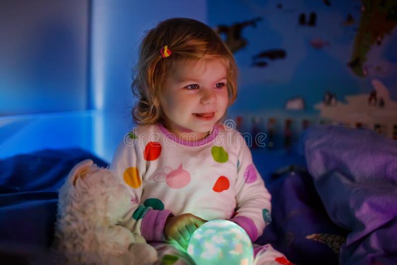 Śliczna mała berbeć dziewczyna bawić się z kolorową nocy światła lampą przed iść łóżko Śpiąca zmęczona dziecko córka wewnątrz fotografia stock