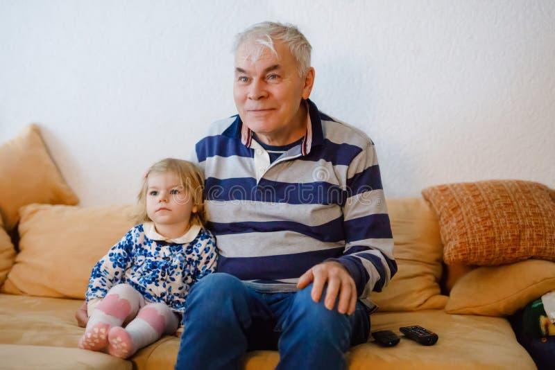 Śliczna mała berbeć dziewczyna, dziad ogląda wpólnie programa telewizyjnego i Dziecko wnuczka i szczęśliwy przechodzić na emerytu fotografia royalty free