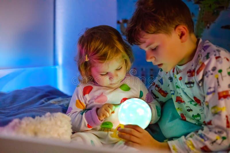 Śliczna mała berbeć dziewczyna i dzieciak chłopiec bawić się z kolorową nocą zaświecamy lampę przed iść łóżko Śpiący zmęczony dzi obrazy royalty free