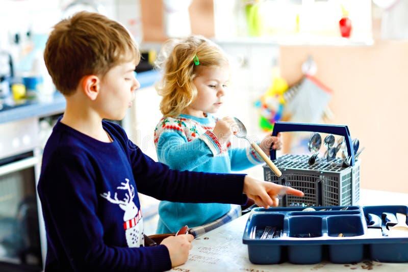 Śliczna mała berbeć dziewczyna i szkolna chłopiec pomaga w kuchni z naczynie pralką Szczęśliwy zdrowy dzieci sortować obrazy royalty free