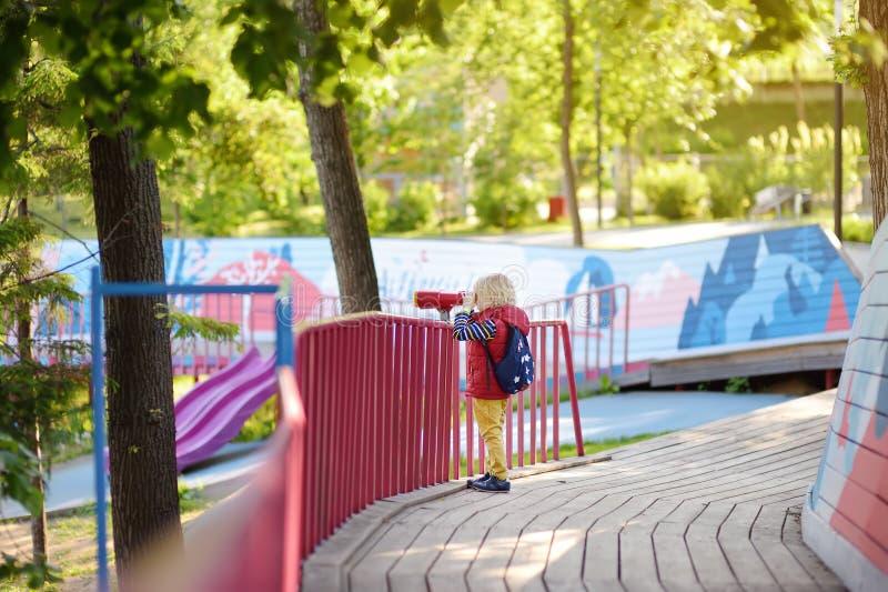 Śliczna mała blond caucasian chłopiec, dzieciak lub dziecko patrzeje przez lornetek na boisku outdoors, obraz royalty free