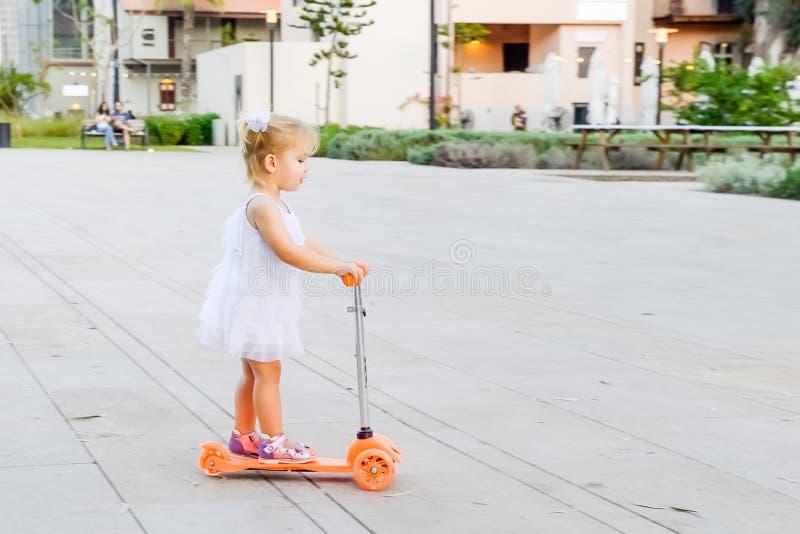 Śliczna mała blondy berbeć dziewczyna w smokingowej jeździeckiej hulajnoga w miasto parka rekreacyjnym terenie z baldachimem, par fotografia stock