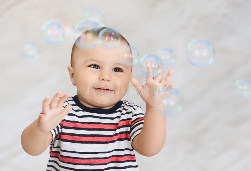 Śliczna mała chłopiec bawić się z wiele mydlanymi bąblami obrazy royalty free