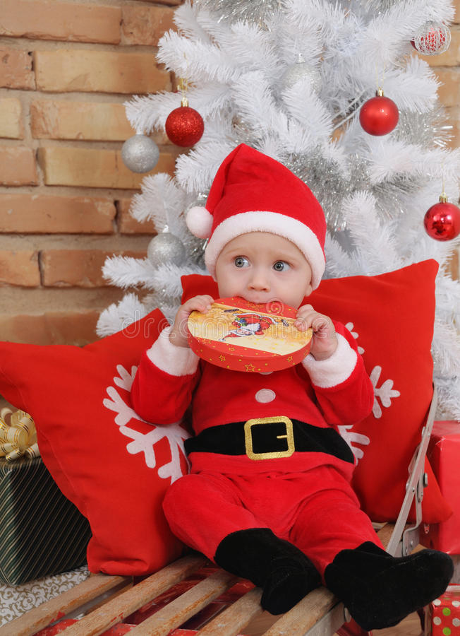 Śliczna mała chłopiec w Santa kostiumu na starym rocznika saniu z prezentem zdjęcie stock