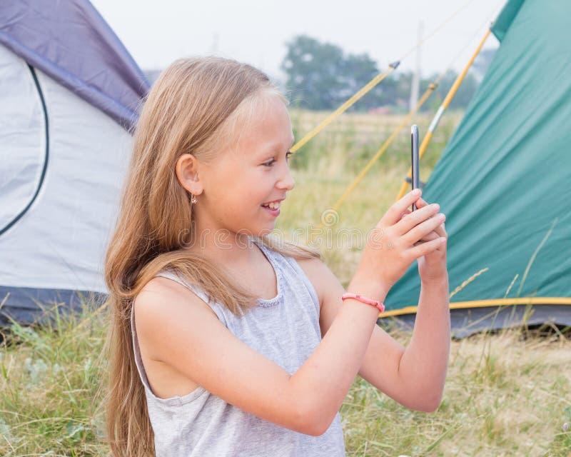 Śliczna mała dziewczyna z długim blondynem bierze obrazek na smartphone na tle namioty obraz royalty free