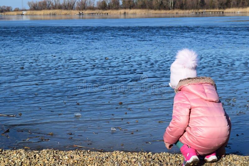 Śliczna mała dziewczynka bawić się blisko jeziora w jesień parku Zimna temperatura fotografia royalty free