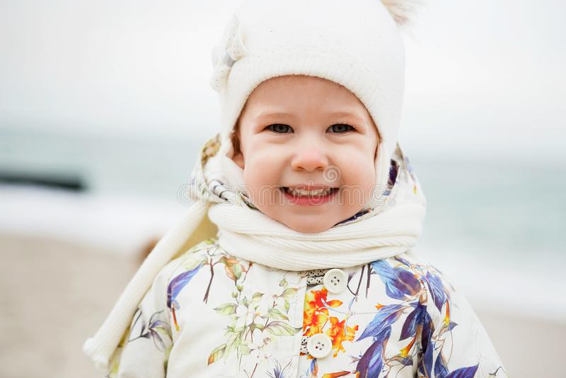 Śliczna mała dziewczynka bawić się na piaskowatej plaży Szczęśliwy dziecka być ubranym obrazy stock