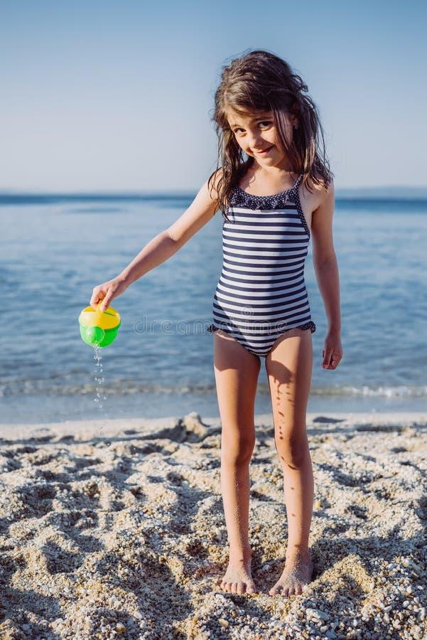 Śliczna mała dziewczynka bawić się na plaży obrazy royalty free