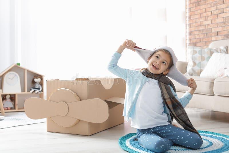Śliczna mała dziewczynka bawić się z kartonowym samolotem obraz stock