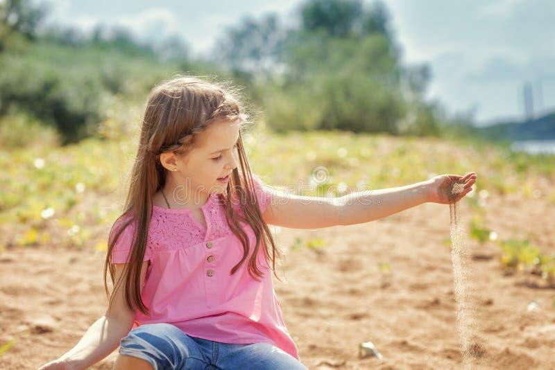 Śliczna mała dziewczynka bawić się z piaskiem w parku fotografia stock