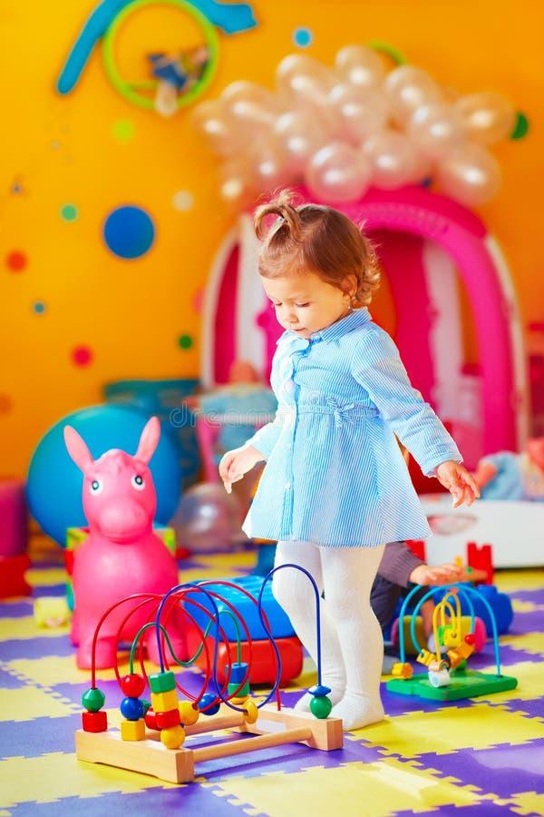 Śliczna mała dziewczynka bawić się z zabawkami w dziecinu obraz stock