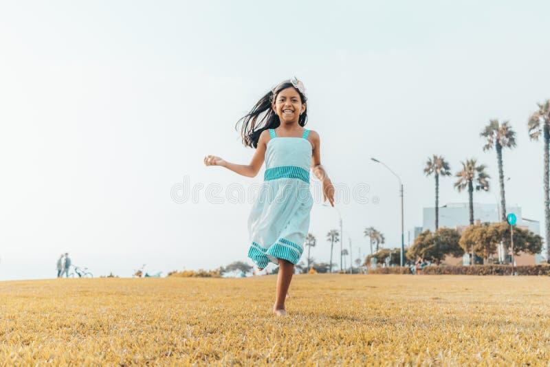 Śliczna mała dziewczynka biega wolno na trawie obraz stock