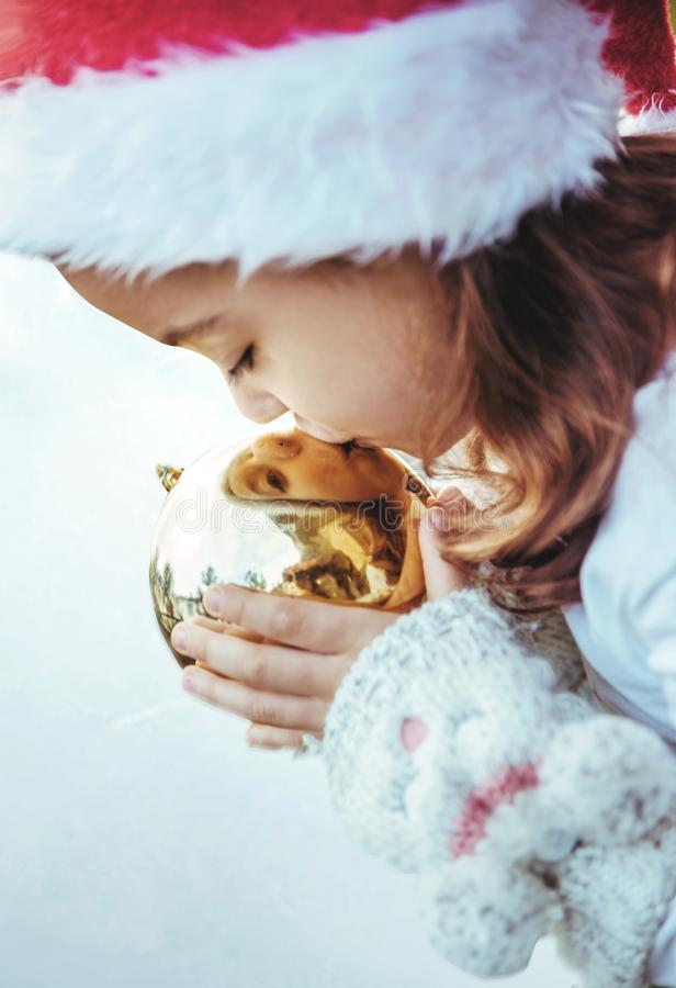 Śliczna mała dziewczynka całuje złotego, boże narodzenie szklana piłka fotografia royalty free