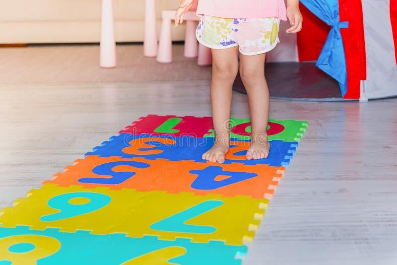 Śliczna mała dziewczynka chodzi i skacze nad sztuki matą zdjęcie stock