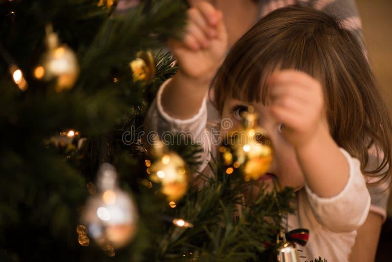 Śliczna mała dziewczynka dekoruje choinki obraz stock