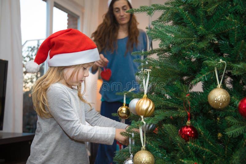 Śliczna mała dziewczynka dekoruje choinki i jej macierzystego lookin obrazy stock
