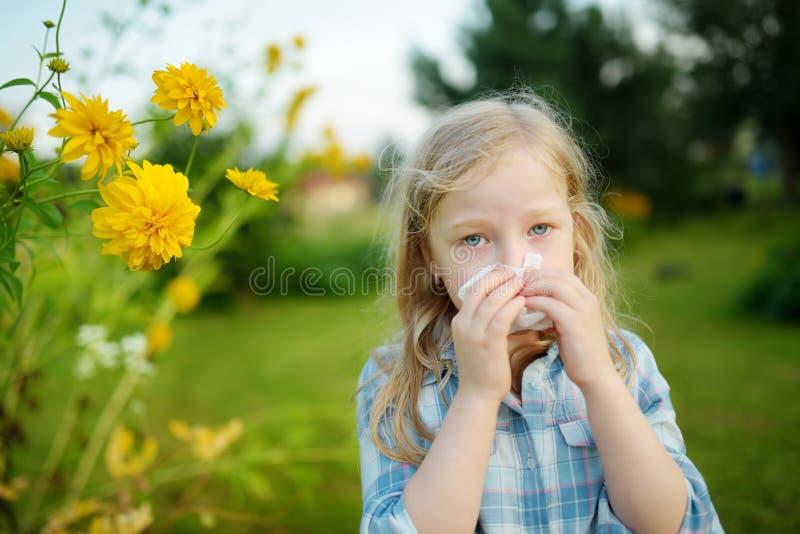 Śliczna mała dziewczynka dmucha jej nos pięknymi żółtymi coneflowers na letnim dniu Alergii i astmy zagadnienia w małych dzieciak zdjęcie stock