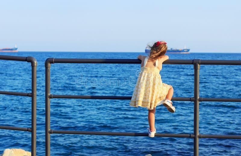Śliczna mała dziewczynka jest przyglądająca słońce nur w szerokim morzu fotografia royalty free