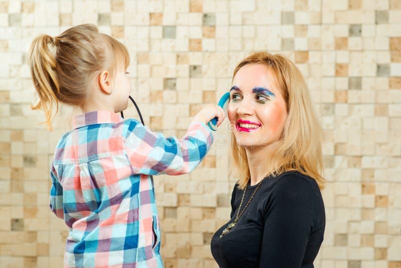 Śliczna mała dziewczynka jest robić śmieszny robi do jej matki obraz royalty free