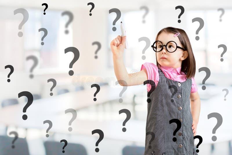 Śliczna mała dziewczynka jest ubranym biznes suknię i pisze znaku zapytania Biurowy tło obraz royalty free
