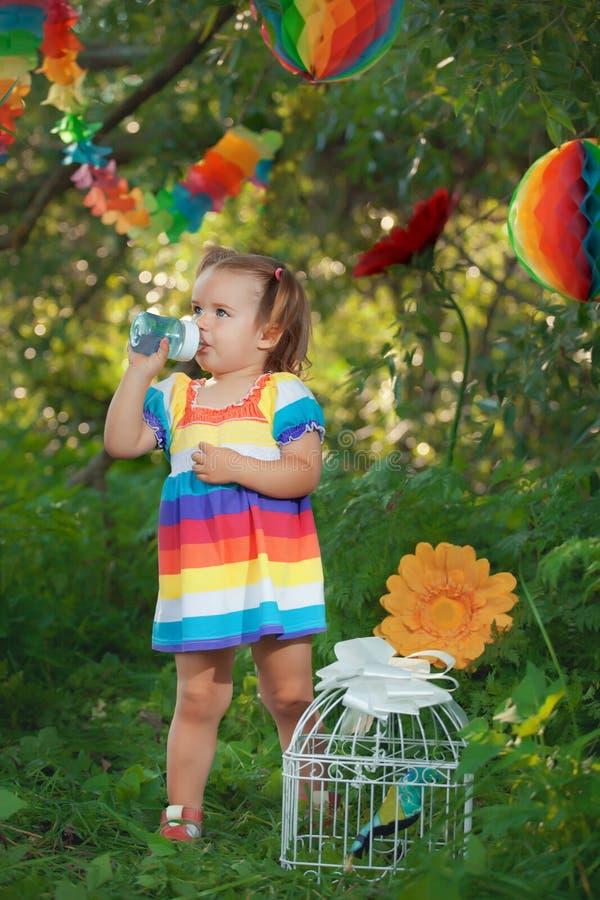Śliczna mała dziewczynka jest ubranym kolorową smokingową wodę pitną obraz stock