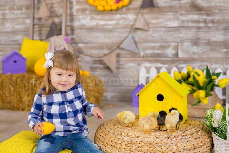 Śliczna mała dziewczynka jest ubranym nieociosanych cajgi bawić się kryjówkę przy haystack aport z kurczaka obsiadaniem - i - Poj obrazy royalty free