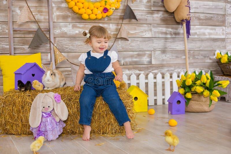 Śliczna mała dziewczynka jest ubranym nieociosanych cajgi bawić się kryjówkę przy haystack aport z kurczaka obsiadaniem - i - Poj zdjęcie stock