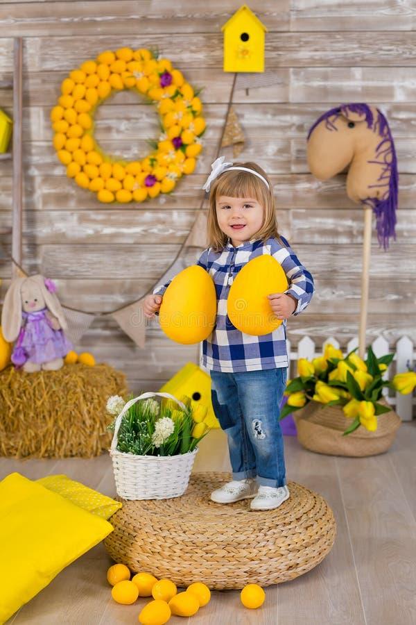 Śliczna mała dziewczynka jest ubranym nieociosanych cajgi bawić się kryjówkę przy haystack aport z kurczaka obsiadaniem - i - Poj obrazy stock