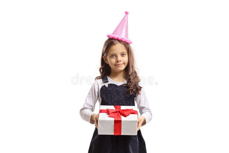 Śliczna mała dziewczynka jest ubranym partyjnego kapelusz i trzyma teraźniejszość obraz stock