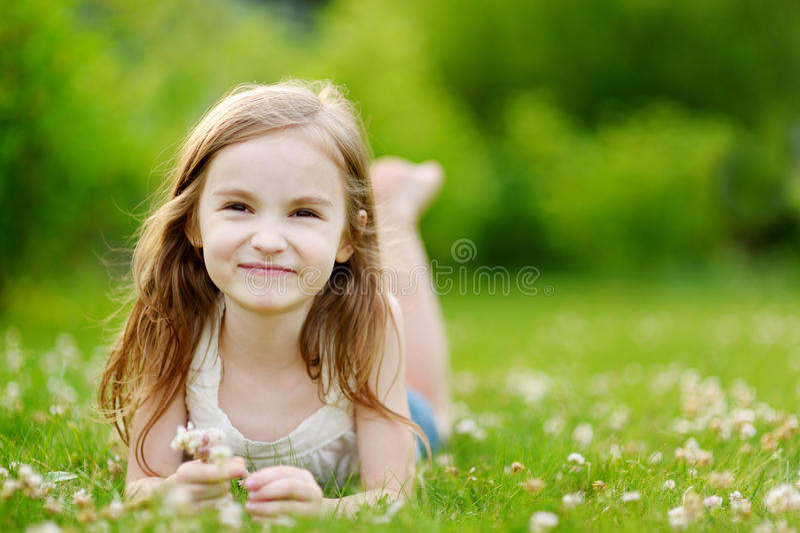 Śliczna mała dziewczynka Kłaść w trawie zdjęcia royalty free