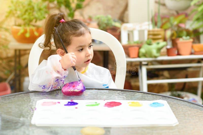 Śliczna mała dziewczynka ma zabawę, barwiący z muśnięciem, bawić się i malować, Preschooler z farbą przy ogródem zdjęcia royalty free