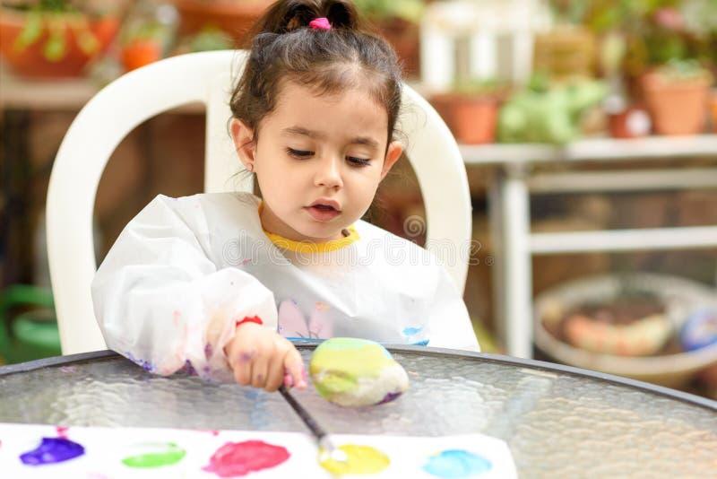 Śliczna mała dziewczynka ma zabawę, barwiący z muśnięciem, bawić się i malować, Preschooler z farbą przy ogródem zdjęcia stock