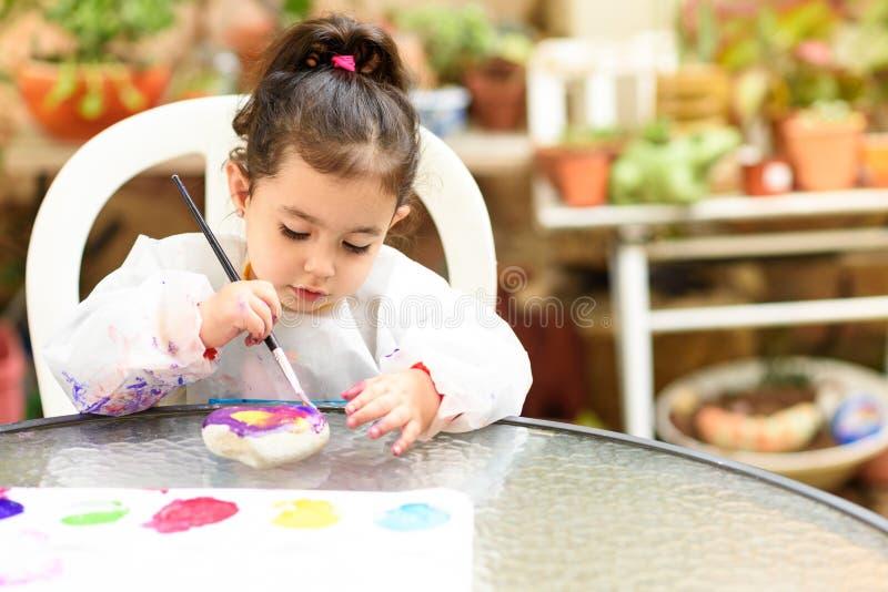 Śliczna mała dziewczynka ma zabawę, barwiący z muśnięciem, bawić się i malować, Preschooler z farbą przy ogródem zdjęcie royalty free
