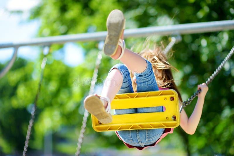 Śliczna mała dziewczynka ma zabawę na boisku zdjęcia stock