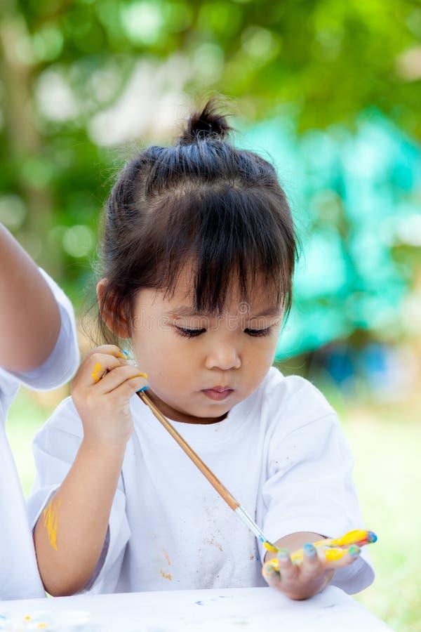 Śliczna mała dziewczynka maluje na jej ręce zdjęcia royalty free