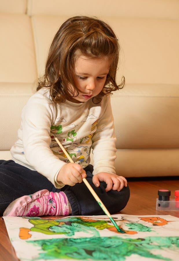 Śliczna mała dziewczynka maluje w domu obraz stock