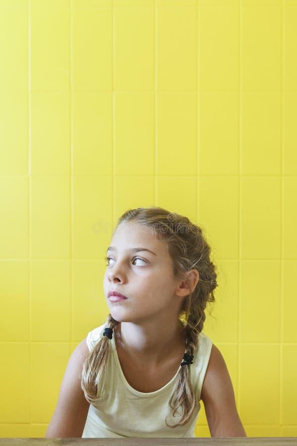 Śliczna mała dziewczynka na żółtym tle z warkoczami fotografia royalty free