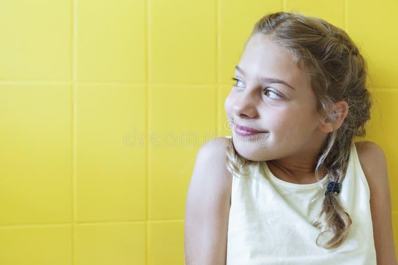Śliczna mała dziewczynka na żółtym tle z warkoczami obrazy royalty free