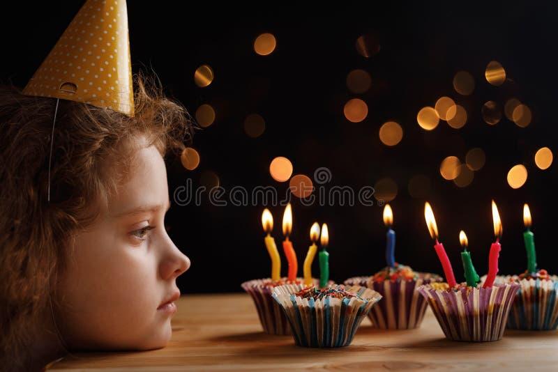 Śliczna mała dziewczynka patrzejący świeczki na urodzinowych tortach obrazy stock