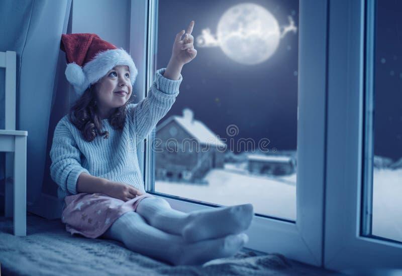 Śliczna mała dziewczynka patrzeje księżyc zimy niebo obrazy stock