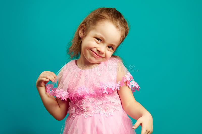 Śliczna mała dziewczynka pozuje w sukni naprzód odizolowywał błękit obraz stock