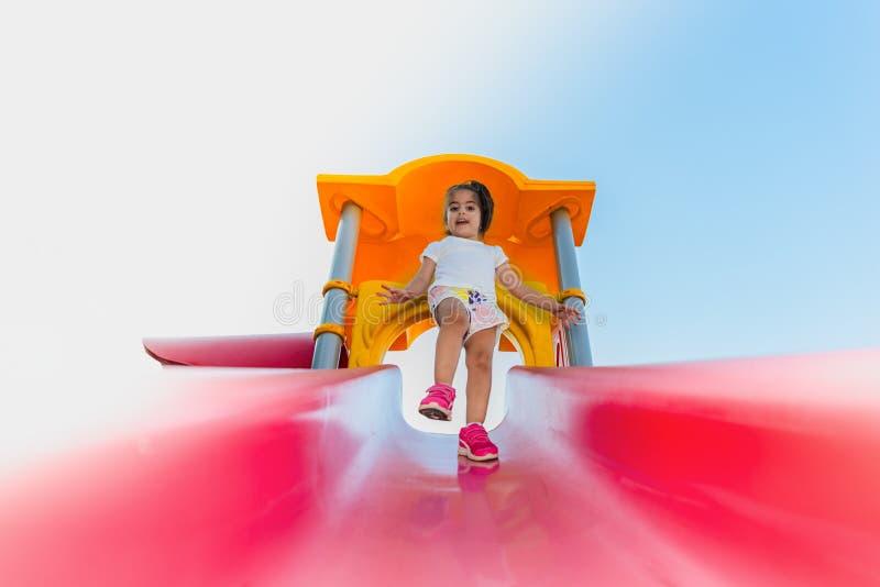 Śliczna mała dziewczynka próbuje chodzić na suwaku zdjęcie royalty free