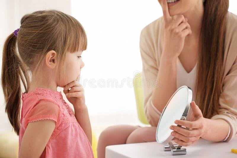 Śliczna mała dziewczynka przy mowa terapeuta obraz royalty free