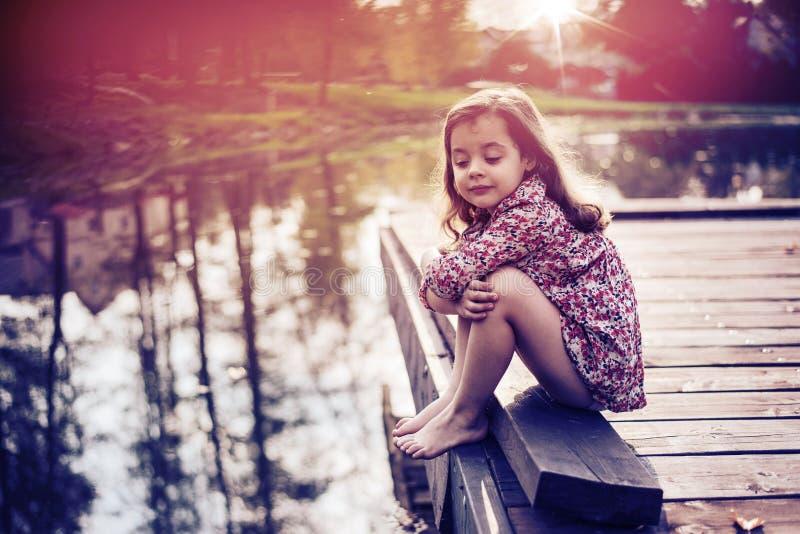 Śliczna mała dziewczynka relaksuje jeziorem fotografia stock