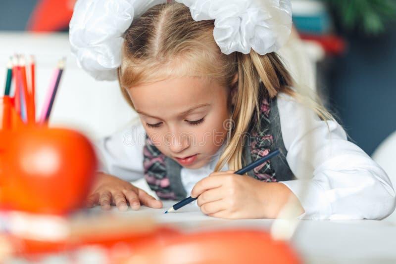 Śliczna mała dziewczynka robi pracie domowej, zbliżenie Uroczy uczennica rysunku obrazek z barwionymi ołówkami podczas gdy siedzą obraz stock