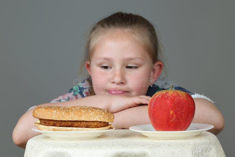 Śliczna mała dziewczynka robi wyborowi między hamburgerem i jabłkiem fotografia stock