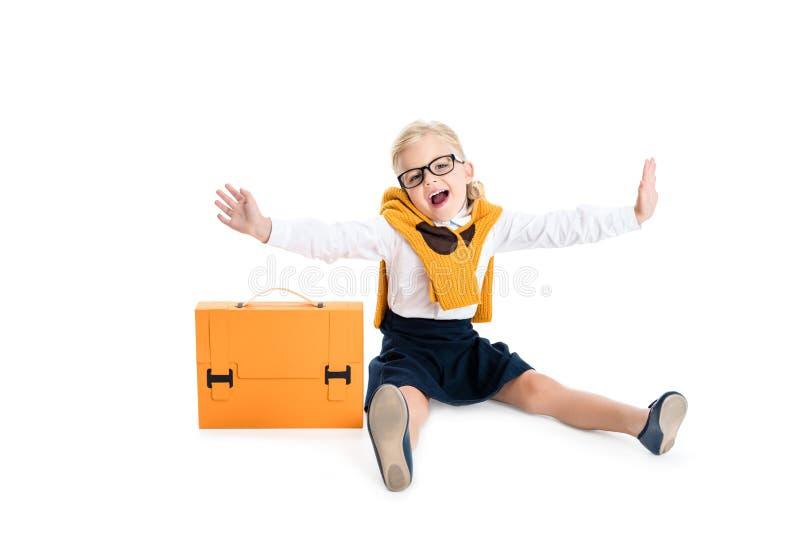 śliczna mała dziewczynka siedzi z teczką i ono uśmiecha się przy kamerą w eyeglasses zdjęcia stock