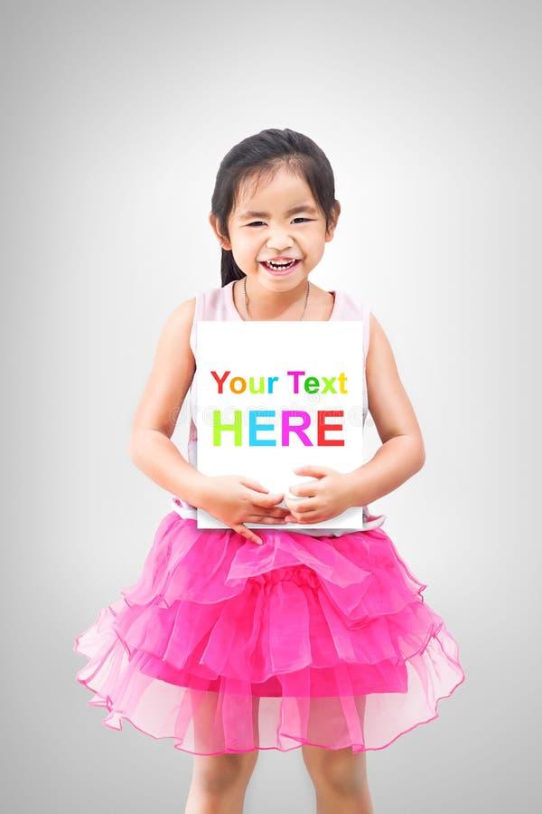 Śliczna mała dziewczynka trzyma białą deskę odizolowywająca na popielatym tle obrazy stock