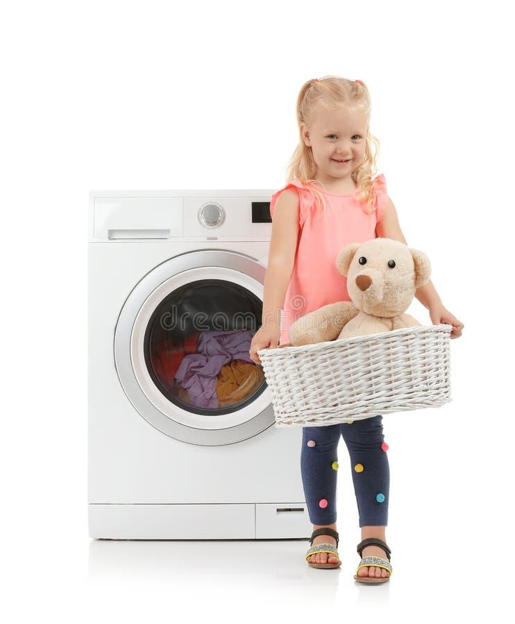 Śliczna mała dziewczynka trzyma pralnianego kosz z misiem blisko pralki zdjęcie stock