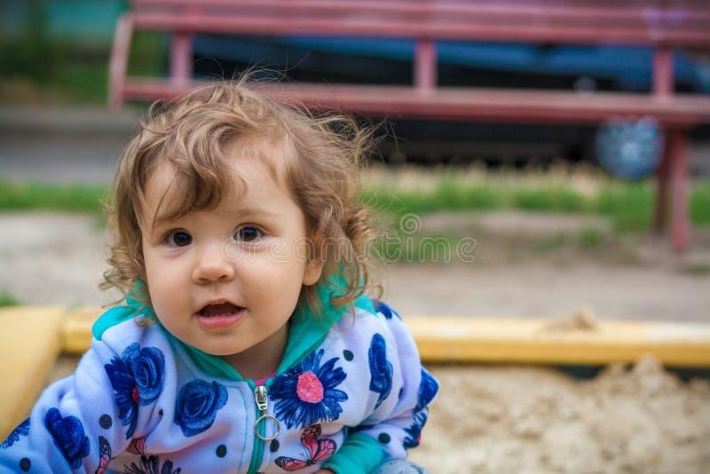 Śliczna mała dziewczynka uśmiecha się bawić się w piaskownicie fotografia royalty free
